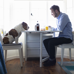 Man eating at the table with his dog