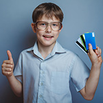 kid holding credit cards
